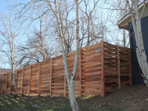 Wooden fencing, cedar basket weave with 4x4 inch posts and 1x4 slats.
