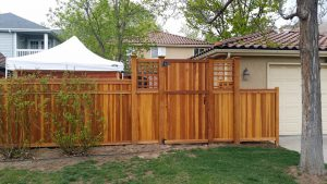 Wooden fence, flat top gate with basket weave lites, and a tongue and groove privacy design with 4 inch cedar posts and cap rail