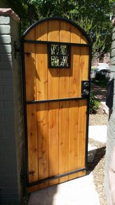 Wooden arch top door-style gate with metal frame and four-square metal window.