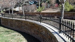 Curved two-rail, spear topped picket metal fence atop a stone wall