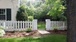 Dog-ear, wide picket fence with arch-top wrought iron metal gate