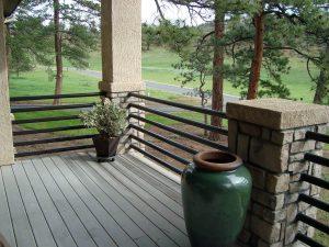 Metal, modern horizontal round rail steel fence embedded in stone pillars