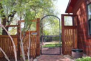 Wood and metal fence with 4 inch heavy wire inserts in arch-top metal gate.
