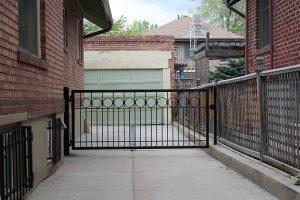 Modern, single driveway metal gate with 8 inch steel rings, powder coated