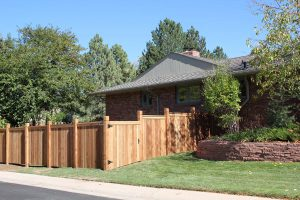 Wooden fencing, cedar privacy fence with wide access gate and decorative notched top 6 inch posts and cap rail