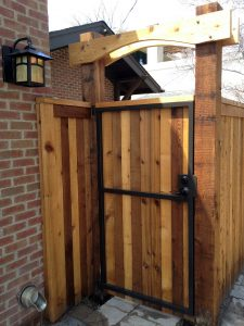 Side yard gate with steel frame and decorative wooden arch element