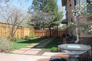 Decorative arbor with privacy cedar fence with woven wood in oversize top section.