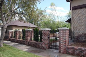 Metal fence and gate, three rail, alternating height pickets, steel inserts between brick pillars.