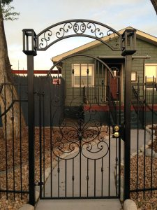 Gate at Fence Right - ached gate with wrought iron inserts and arch top arbor