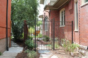 Metal fence and gate with alternative picket height and detail in ached top of gate section (right). Round top gate.