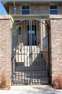 Double arch top steel gate wrought iron handrail and steel fencing mounted on retaining wall