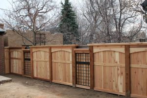 wood and metal fencing: privacy fence with metal trellis inserts and arched top and flat cap details.