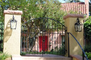 Double metal arch top gate with wrought iron inserts and handrail on steps