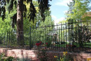 Side view of solid steel three rail, four foot fence with 4 post decorative corner posts with twist and alternating height details