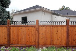 Metal and wood fencing. Tongue and groove wooden privacy fence with steel 4-inch rings in rectangular pattern on top rail.