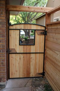 Wooden arch top door-style gate with custom Zia metal window insert with tongue and groove wooden privacy fence with double open top rail.